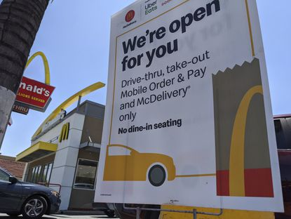 A sign seen May 20, 2020, warns there is no dine-in seating at a McDonald's restaurant in Los Angeles. McDonald's sales are gradually improving; it said June 16 that global same-store sales were down 21% in May. That was an improvement from April's 39% decline.