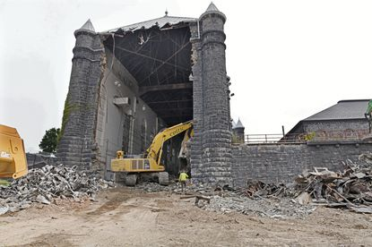 Construction machine and workers doing the demolition of the old Baltimore City Jail, built in the early 1800s as the Maryland Penitentiary and has been owned by the state since 1991.