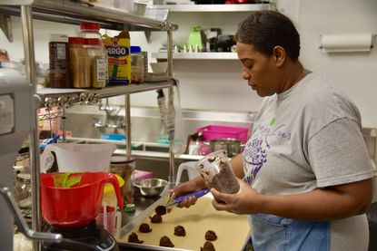 Kora Polydore loads up a baking sheet of brownie batter Tuesday afternoon in the kitchen of her new bakery, Kora Lee's Gourmet Dessert Cafe, at 6421Fredrick Road in Catonsville.