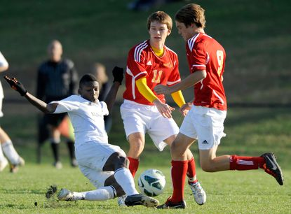McDonogh's Erumuse Momoh, left, slides to get a ball away from Calvert Hall's Steve Walters, center, and Jacob Bender in the first half of their MIAA A Conference semifinal Tuesday.