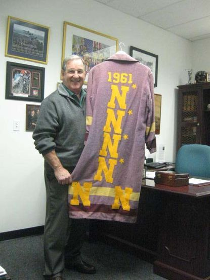 Joe Bellino poses with an Army bathrobe he won on a bet as a player at Navy.
