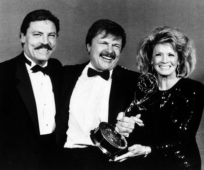 """Actor John Karlen, center, who portrays the husband of detective Mary Beth Lacey on the TV show """"Cagney & Lacey, """" posing with presenters Stacy Keach, left, and Angie Dickinson after Karlen won an Emmy for best supporting actor at the Emmy Awards in Pasadena, Calif. Sept. 21, 1986."""