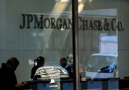 Vehicles are reflected in a window at JPMorgan Chase & Co. offices in New York.