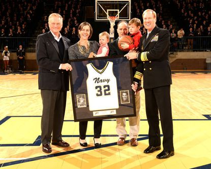 Becky Dowling Calder participated in a ceremony to retire her Navy basketball jersey with her husband, Adrian Calder, two children, athletic director Chet Gladchuk, left, and academy Superintendent Vice Adm. Michael Miller, right.