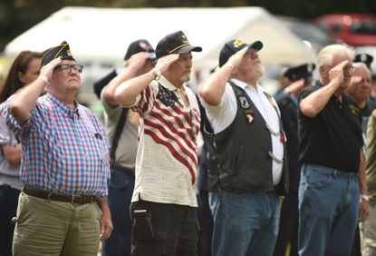 A line of veterans salute the flag as the national anthem is sung during a 9/11 Remembrance event held at the Molleville Farm VFW Post 467 on Saturday, Sept. 11, 2021.