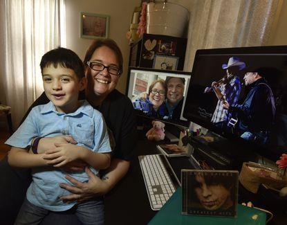 Longtime Garth Brooks fan Hope Witt poses with her son, William, next to Brooks photographs and memorabilia in her Glen Burnie home. Witt has tickets for all five Royal Farms Arena shows.