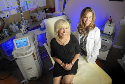 Grace Ban of Odenton, left, teamed with her doctor, Beth Comeau, to undergo a facial treatment in which Ban's blood was injected to reduce acne scars and wrinkles.