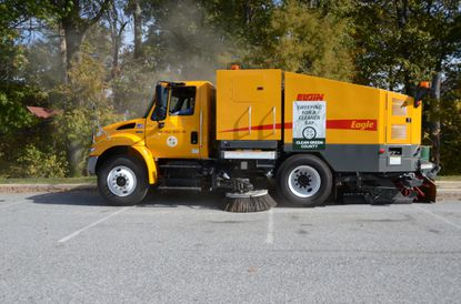 """Baltimore County Executive Kevin Kamenetz takes a spin in one of the county's new street-sweeping trucks during a demonstration at Wilson Point Park in Middle River Tuesday. The county is using stormwater remediation fees - dubbed the """"rain tax"""" by opponents - to revive a street-sweeping program. By removing debris from streets, less sediment and nutrients wash into creeks and rivers that feed the Chesapeake Bay."""