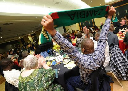 Boniface Sakala, of Zambia, holds up a banner celebrating his country during a presentation on Zambia's soccer victory in the African Cup of Nations during the second annual Celebrating Africa event at McDaniel College in Westminster Monday night.