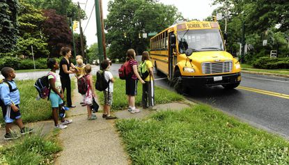 Students from the Idlewylde neighborhood prepare on June 3 to load onto a county school bus headed to Stoneleigh Elementary School temporarily housed at Carver Center. Idlewylde residents are concerned that their children could be redistricted out of the Stoneleigh district by school officials as a means of easing overcrowding throughout the Towson area.