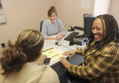 Nurse Sarah Breedlove, center, and Spanish-language interpreter Carydad Nussa, right, assist a patient at one of Baltimore County's family planning clinics.