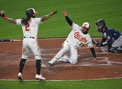 Orioles' Freddy Galvis, left, signals safe as teammate Anthony Santander, center, scores in front of Mariners catcher Luis Torrens in the third inning of the second game of a doubleheader on April 13, 2021 at Orioles Park at Camden Yards.