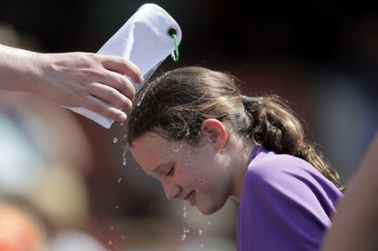 """A young spectator gets water doused on her by an adult during the seventh inning of a baseball game between the Orioles and the Boston Red Sox on Sunday at Camden Yards. The Orioles won, 5-0. The National Weather Service says the """"oppressive and dangerous"""" heat wave will abate by Monday and Tuesday."""
