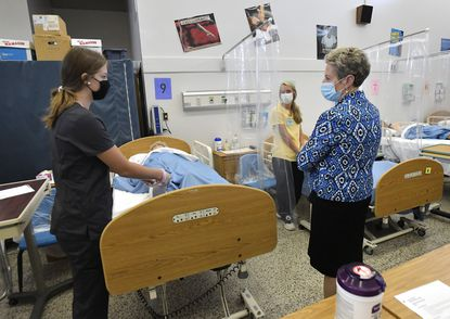 Karen Salmon, state superintendent of schools, stops to talk with Liberty seniors Amanda Cyran, left, and Emma Bauer as they work in the Certified Nursing Assistant lab during her visit to the Carroll County Career and Tech Center in Westminster Tuesday, Oct. 6, 2020.