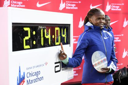 Brigid Kosgei of Kenya, poses with her time after winning the Women's Bank of America Chicago Marathon while setting a world record of 2:14:04, Sunday, Oct. 13, 2019, in Chicago.