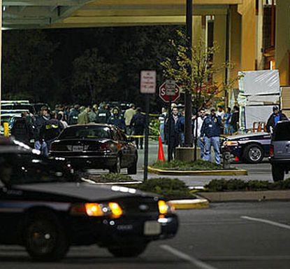 Police officers surround the area next to a Home Depot store near Seven Corners, Va., Monday night after a woman was shot and killed in the parking lot.