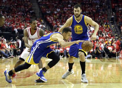 Golden State Warriors' Stephen Curry, center, dribbles past teammate Andrew Bogut, right and Houston Rockets' Trevor Ariza, left, before his knee injury during the first half in Game 4 of a first-round NBA basketball playoff series on Sunday.