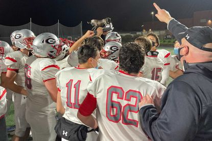 The Glenelg football team raises the Elgard trophy after defeating Howard 26-21 on Friday, April 9, 2021.