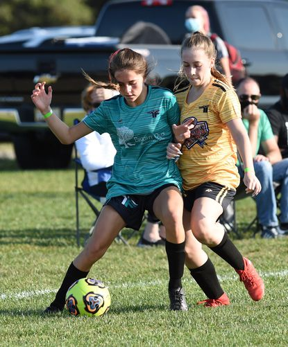 Togo SC player Ava Wheeler, left, and Venom's Brianna McArdie battle for control of the ball during opening night of the Top Flight Girls Soccer league Tuesday at Carsin's Run Fields.