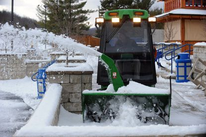 Liberty Mountain Resort lodge maintenance worker Brian Dick, of Fairfield, Pa., clears snow from the patio with a snow plow.