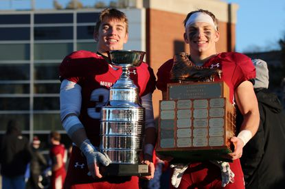 Spencer Kirin (left) with the Sodexo Trophy, which goes to the winner of the Muhlenberg-Moravian game, and Max Kirin with the Centennial Conference trophy. The Kirin brothers play on the Muhlenberg football.