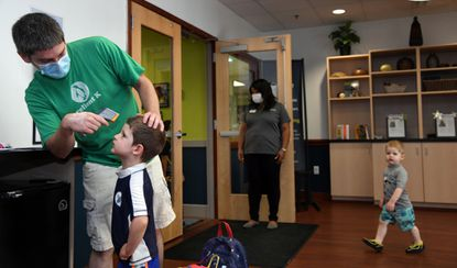 Chris Baldelli of Lutherville checks the temperature of his 4 year old son Alex Baldelli as his other son Theo walks by behind them. Celebree School director Sapphire Jackson holds the door open from the lobby at the center in Lutherville. Parents use their own thermometers to check temperatures, which are then recorded by the school. July 29, 2020