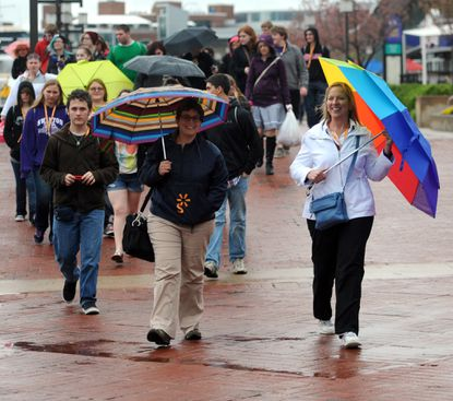 Pam Kazmierczak, Swanton, OH, director of the Swanton Marching Band from Swanton High School, carries a colorful umbrella to protect her from wind and rain as she walks in the Inner Harbor with 52 band members and 11 chaperones. She was to lead the band in a concert at the Harborplace Amphitheater, but the event was cancelled because of the rain. They are going to the National Aquarium in Baltimore instead.