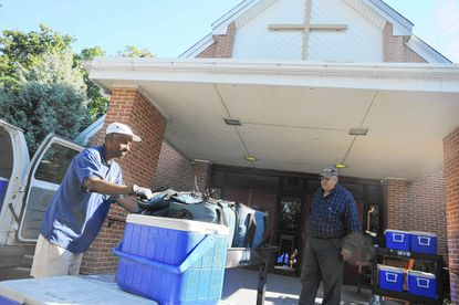 Howard Mitchell, left, a Meals on Wheels employee, delivers hot and cold meals to Phillip Douglas, site coordinator of the new Meals on Wheels site at St. Thomas Episcopal Church in Towson Aug. 15.