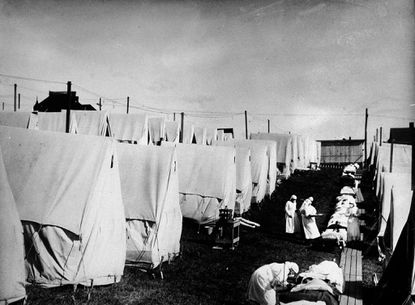 Nurses care for victims of a Spanish influenza epidemic outdoors amidst canvas tents during an outdoor fresh air cure in Lawrence, Massachusetts, 1918 (Hulton Archive/Getty Images/TNS)