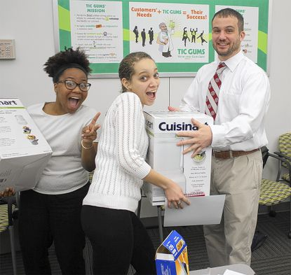 Tara Coley, left, and Kim Scott, center, both students at Harford Tech, receive their home ice cream makers from Tim Andon at the 2014 Ice Cream University graduation.