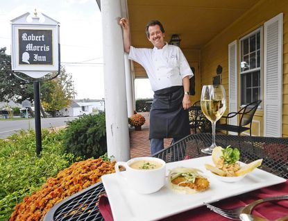 The historic Robert Morris Inn has been restored by chef/proprietor Mark Salter, who was the executive chef of the Inn at Perry Cabin for 17 years. Salter is pictured in the terrace with starter A Taste of the Chesapeake, consisting of (l-r) cream of crab soup, fried Maryland oyster with remoulade and smoked Blue fish pate.