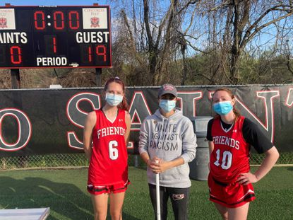 From left, Friends' Carlie Koch, coach Meg Milliman and Paige Saudek pose after a 19-8 win over Concordia Prep.