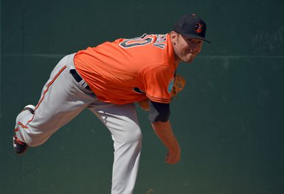 Baltimore Orioles pitcher Chris Tillman follows through on a pitch at the first day of workouts for position players as well as pitchers and catchers on the field during spring training at the Ed Smith Stadium complex.