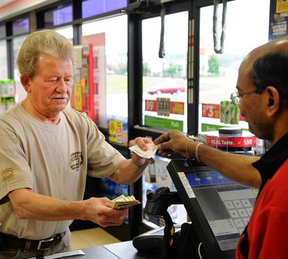 Rick Krall, of Forest Hill, takes his chances with Powerball as 7-Eleven employee Vick Reddy hands over the tickets Tuesday afternon at the 7-Eleven in Hickory.