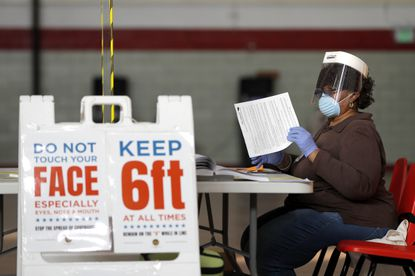 Louisa Boyer, a provisional election judge, reviews paperwork at a voting center at Edmondson High School as voters arrive to cast their ballot in the 7th Congressional District special election, Tuesday, April 28, 2020, in Baltimore. The latest challenge to face city voters? Late arriving ballots for the June 2 primary. (AP Photo/Julio Cortez)