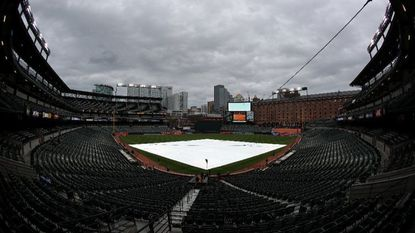 The tarpaulin covers the infield at Camden Yards on Tuesday. The postponement gave the Orioles a much-needed night off. The cost? They'll have to play 27 games in 27 days.