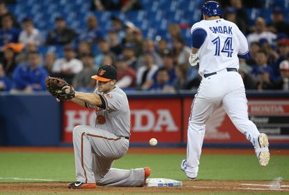 Justin Smoak of the Toronto Blue Jays reaches first base on a throwing error to Chris Davis of the Baltimore Orioles by Manny Machado in the eighth inning during MLB game action on April 22, 2015 at Rogers Centre in Toronto.
