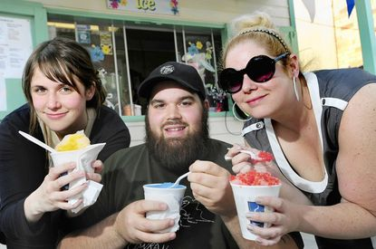 """The Snowball Collective is a threesome that is studying the """"snoball,"""" and just came out with a Snoball Guide. They are shown (l-r) Katie Lambright, Bruce Blume and Sara Tomko at one of their favorite snoball stands, Dean's on Harford Road."""