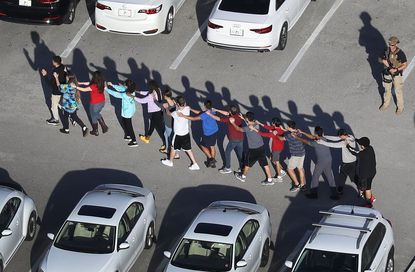 Students and others are brought out of the Marjory Stoneman Douglas High School after a mass shooting on Feb. 14, 2018 in Parkland, Florida.