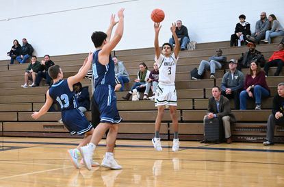 Century's Chris Burriss (3) releases a shot from three-point range as a pair of Catoctin opponents try to defend on the play, in the holiday basketball tournament at Liberty High School on Thursday, Dec. 26.