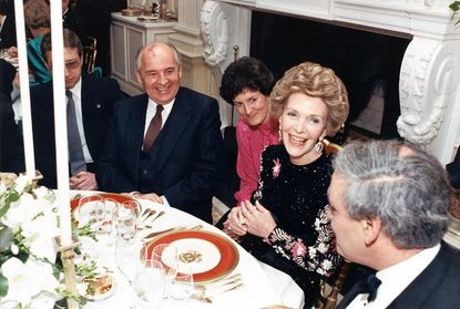 First lady Nancy Reagan presides over a state dinner in honor of Soviet president Mikhail Gorbachev in 1987. The place settings feature the red dinner plates she helped design.