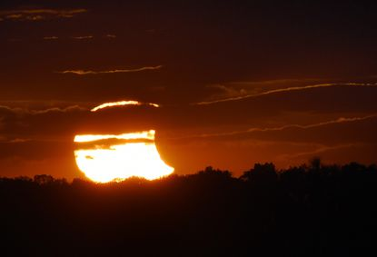 The sun breaks through heavy cloudcover revealing a partial solar eclipse at sunset on Oct. 23, 2014.