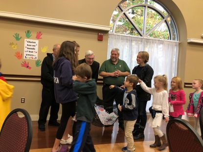 Father Neville O'Donohue, pastor at St. John Catholic Community, and Deacon Mike welcome children as they place their fish (with prayers and thanks) into the fish net during Clergy Appreciation Day.