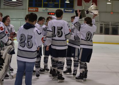 Members of the Marriotts Ridge ice hockey team pose with the Serio Cup after defeating Glenelg on March 1, 2021.