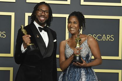 """Matthew A. Cherry, left, and Karen Rupert Toliver, winners of the award for best animated short film for """"Hair Love,"""" pose in the press room at the Oscars on Sunday at the Dolby Theatre in Los Angeles."""