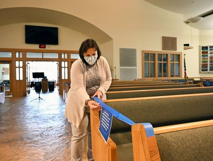 St. Matthew Lutheran Church employee Julie McDonnell secures fresh tape on pews Thursday, April 1, 2021 for social distancing in preparation for upcoming Easter services. Facemasks are mandatory and social distancing practices are established in the sanctuary for services.