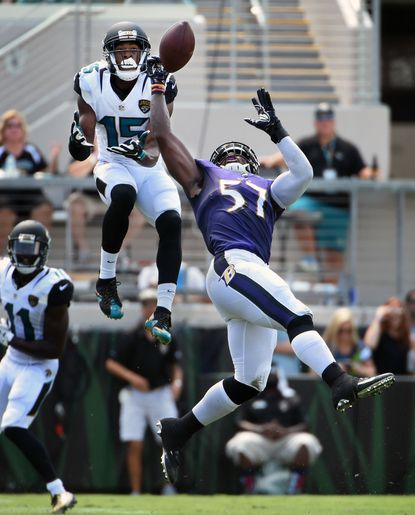 The Ravens' C. J. Mosley, right, intercepts a pass intended for the Jaguars' Allen Robinson, in the first quarter last week.