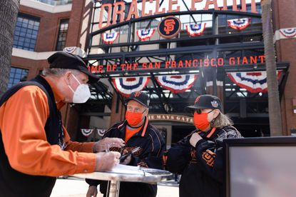 San Francisco Giants fans Dave Harding of San Leandro, center, and his wife, Nancy Faltisek, check in at one of the vaccination/negative test verification booths to show the proof of their COVID-19 vaccinations before being admitted to Oracle Park at the Giants' season home opener on Friday, April 9, 2021, in San Francisco, California. (Dai Sugano / Bay Area News Group/Tribune News Service)