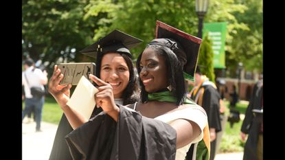 Tiffany Afoakwa, right, takes a selfie with fellow graduate Giselle Gonzalez before the 149th commencement ceremony for McDaniel College on Saturday, May 25.