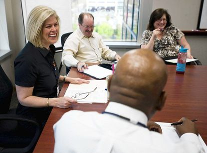 Laura Neuman, left, CEO of the Howard County Economic Development Authority, shares a laugh with members of her team during a staff meeting.